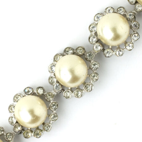 Close-up view of faux pearls on rings of diamante