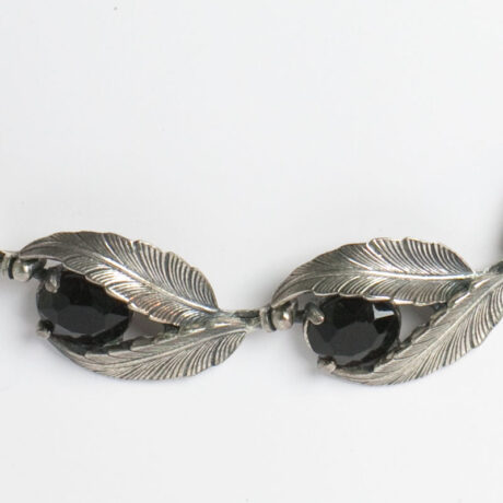 Close-up view of onyx glass stones nestled in silver-tone leaves