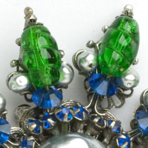 Close-up view of emerald bead, peal, and sapphire stone accents