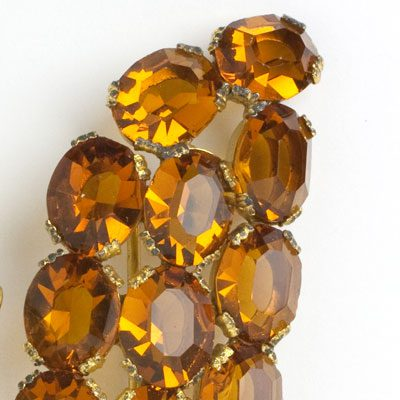 Close-up view of faceted, oval golden-topaz stones oval