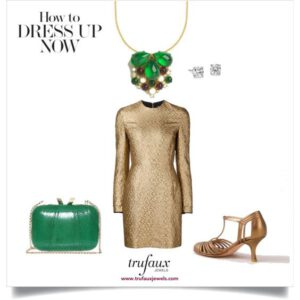 Dress clip on chain adorning gold dress with emerald bag